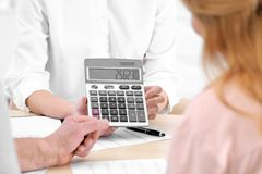 Insurance agent showing calculator with value stock photo