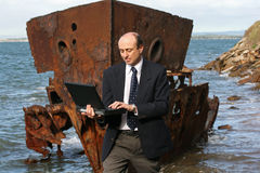 Insurance assessor. Businessman on the beach by an old wreck, dressed in business attire in front of a very old rusting shipwreck on the beach, with his laptop stock images