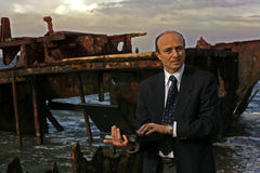 Insurance assessor. Businessman on the beach by an old wreck, dressed in business attire in front of a very old rusting shipwreck on the beach, with his laptop stock image