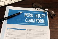 Insurance: blank work injury claim form. On desk