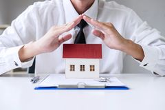 Insurance and care protection of house concept, businessman agent with protective gesture of small home model.  stock image