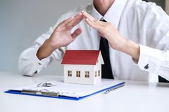 Insurance and care protection of house concept, businessman agent with protective gesture of small home model.  royalty free stock photos