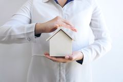 Insurance and care protection of house concept, woman with protective gesture of small home model.  royalty free stock image