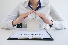 Insurance and care protection of house concept, woman with protective gesture of small home model.  stock photography