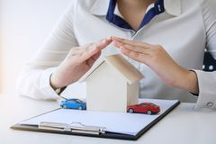 Insurance and care protection of house concept, woman with protective gesture of small home and car model.  stock images