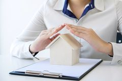Insurance and care protection of house concept, woman with protective gesture of small home model.  stock image