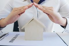 Insurance and care protection of house concept, woman with protective gesture of small home model.  royalty free stock photo