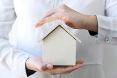 Insurance and care protection of house concept, woman with protective gesture of small home model.  royalty free stock images