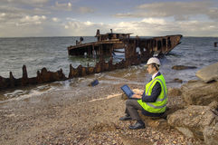 Insurance claim. Businessman sitting on the rocks at the beach with his laptop and with a beautiful old rusting shipwreck in the background stock photo
