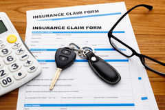 Insurance claim concept with car key and calculator. On wood desk Stock Photo
