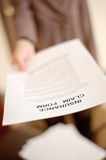 Insurance claim form. Woman showing insurance claim form to you, shallow DOF Stock Images