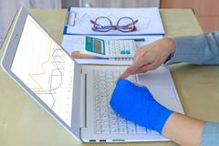 Work injury. injured woman hand sore with blue elastic bandage o. Insurance,claim,sore arm,graphs,calculator,project,technology,home,paper,plan,work,office royalty free stock images