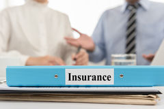 Insurance. Closeup insurance file with two business people meeting in office. Concept of  insurance Stock Image