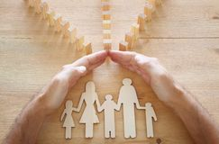 Insurance concept. Businessman protecting a family from domino effect. life, financial and health issues.  royalty free stock photography