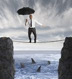 Insurance concept. With businessman on a rope and shark in the sea Royalty Free Stock Photo