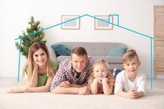 Insurance concept. Contour of house around happy family. Lying on floor at home stock photo