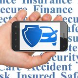 Insurance concept: Hand Holding Smartphone with Car And Shield on display. Insurance concept: Hand Holding Smartphone with  blue Car And Shield icon on display Stock Photography