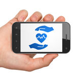 Insurance concept: Hand Holding Smartphone with Heart And Palm on display. Insurance concept: Hand Holding Smartphone with  blue Heart And Palm icon on display Royalty Free Stock Images
