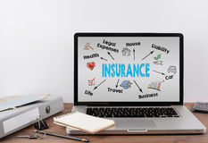 Insurance concept. Office desk with a laptop. Light gray background.  Royalty Free Stock Photos
