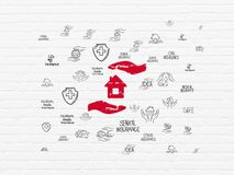 Insurance concept: House And Palm on wall background. Insurance concept: Painted red House And Palm icon on White Brick wall background with  Hand Drawn Stock Image