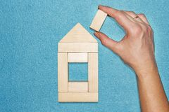 Insurance and construction concept. hand builds house of wooden cubes on blue background. Repair and restoration of house. Royalty Free Stock Images