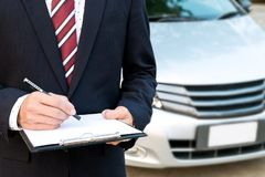 An insurance expert employee working with a car at the outdoor stock image