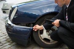Insurance expert examining car damage Stock Images