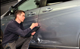 An insurance expert. Man inspecting car damage after an accident stock photography