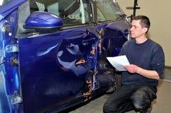 Insurance expert working at damaged car stock image