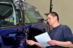 Insurance expert working at damaged car royalty free stock photo