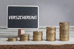Insurance in German language on sign. Versicherung insurance in German language, white chalk type on black board, Euro money coin stacks of growth on wood table royalty free stock image