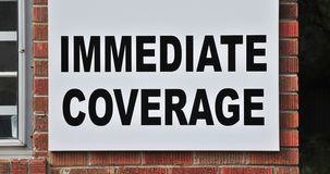 Insurance Immediate Coverage Sign. A sign advertises immediate coverage on insurance for car, home, auto and motorcycles Stock Photo