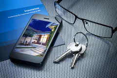 Insurance Keys Cell Phone. A still life of a cell phone, keys, glasses and insurance brochure on a desk royalty free stock photography