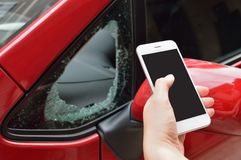 Insurance for my car by vandalism. Man holding the smartphone for calling insurance agency by the vandalism in the car Royalty Free Stock Photo