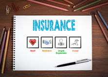 Insurance. Notebooks, pen and colored pencils on a wooden table.  Royalty Free Stock Photo