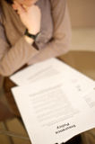 Insurance policy. Woman reading insurance policy paper on desk Stock Photos