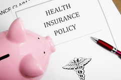 Insurance policy. Health insurance policy and piggy bank Royalty Free Stock Photography
