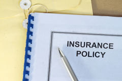 Insurance policy. Folder on desk in office with pen and manila envelop Royalty Free Stock Photo