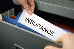 Insurance policy. Business woman seeking an insurance policy in a filing cabinet Stock Photo