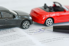 Insurance policy contract concept with toy model cars having a crash Stock Images