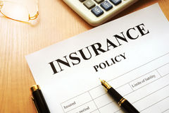 Insurance policy on a desk. Insurance policy and calculator on a desk Royalty Free Stock Images