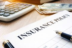 Insurance policy and dollar bills on a desk. Insurance policy and dollar bills on an office desk Stock Image
