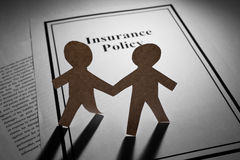 Insurance Policy and Paper Chain Men Royalty Free Stock Image