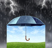 Insurance Protection. Concept with a black umbrella covering and protecting from a dark dangerous thunder rain storm with lightning and under is a peaceful safe Stock Photography