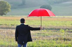 Insurance and protection concept, businessman with umbrella in the field Royalty Free Stock Images