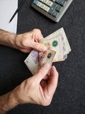 Hands of an older man counting argentine banknotes. Insurance with retirement and protection plan, investment for monthly pensions to adulthood, need of economic royalty free stock photo