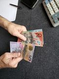 Hands of an older man counting australian banknotes. Insurance with retirement and protection plan, investment for monthly pensions to adulthood, need of royalty free stock photography