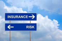 Insurance and risk on blue road sign Stock Photos