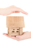 Insurance and safety concept. Small wooden house in a female hands Stock Image