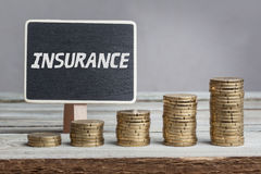 Insurance on sign with money stacks. Word Insurance in white chalk type on black board, Euro money coin stacks of growth on wood table Stock Image